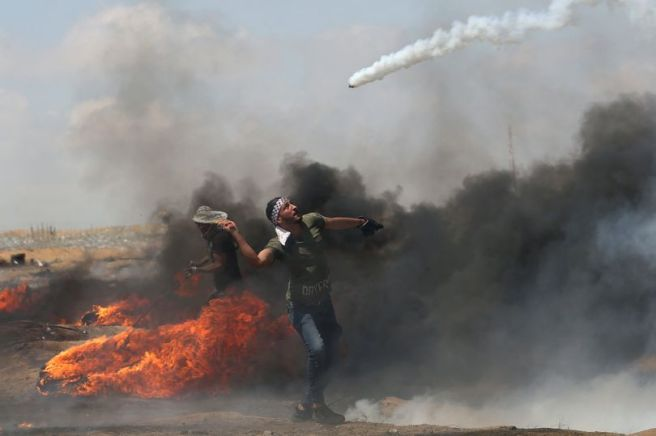 Demonstrator-uses-a-racket-to-return-tear-gas-canister-fired-by-Israeli-troops-during-a-protest-wher